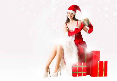 christmas present box: Attractive woman in Santa Clause outfit sitting on the present box and holding Christmas present. Christmas background