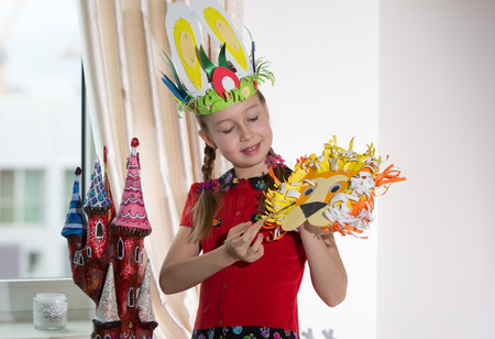 art and craft: Little girl demonstrating her art craft works, Paper masher fairy castle andEaster bonnet she made. Educational and creative concept. Stock Photo