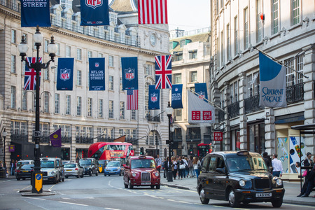 west end: LONDON, UK - OCTOBER 4, 2015: Regent street decorated with British flags. Lots of people walking from shop to shop and public transport, taxis, cars and buses on the road