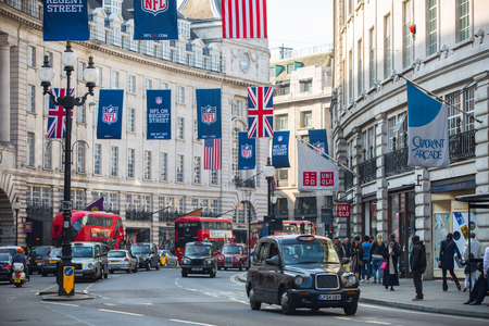 regent: LONDON, UK - OCTOBER 4, 2015: Regent street decorated with British flags. Lots of people walking from shop to shop and public transport, taxis, cars and buses on the road