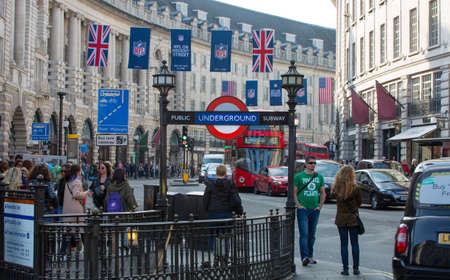 regent: LONDON, UK - OCTOBER 4, 2015: Underground entrance at the Regent street and lots of people and cars on the road
