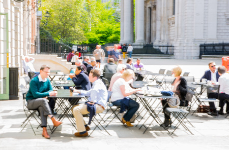 men talking: LONDON, UK - MAY 17, 2016: People having a lunch in cafe in sunny day. Blurred image. City of London business life concept Editorial