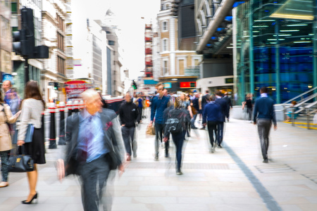 persona caminando: LONDON, UK - MAY 17, 2016: Business people walk through the City of London street. Blurred image. City of London business life concept