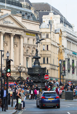 piccadilly: LONDON, UK - OCTOBER 4, 2015: Eros monument at Piccadilly circus and lots of people crossing the road