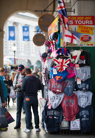 piccadilly: LONDON, UK - OCTOBER 4, 2015: Souvenirs stall in Piccadilly circus with lot of walking people, pedestrians