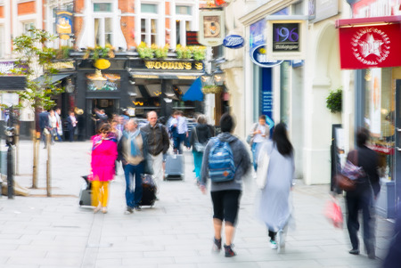 city view: LONDON, UK - MAY 17, 2016: Business people walk through the City of London street. Blurred image with cafes and restaurant view at the background. City of London business life concept