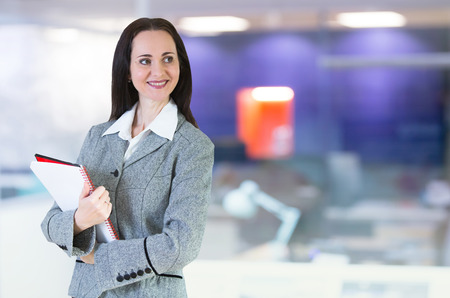 office environment: Attractive woman portrait in office environment with notepad