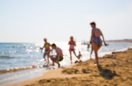 blurred people: Blurred image for background. People on the beach, walking and playing in the sea. Greece Stock Photo