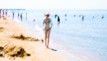 Blurred image of people walking by the water line at beach. Holiday concept. Greece Stock Photo