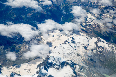 view through: Alps with snow view through the white clouds Stock Photo