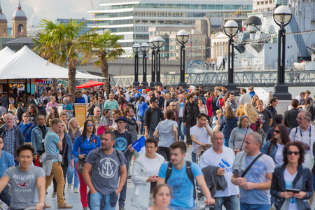 womna: LONDON, UK - SEPTEMBER 20, 2015: Thames embankment with lots of walking people and tourists Editorial