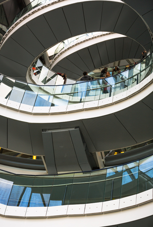 going down: LONDON, UK - SEPTEMBER 19, 2016: Famous spiral staircases of London City Hall with walking people. Modern architectural structure
