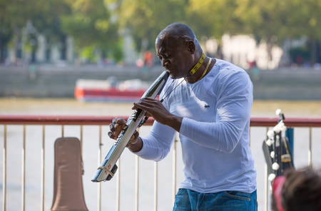 LONDON, UK - SEPTEMBER 20, 2015: Street performance by musician at south embankment of the River Thames