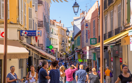 country road: CANNES, FRANCE - 19 SEPTEMBER, 2016: Centre of the town view with restaurants, cafes and lots of walking people. Old city of Cannes colorful houses.
