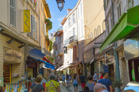 french doors: CANNES, FRANCE - 19 SEPTEMBER, 2016: Centre of the town view with restaurants, cafes and lots of walking people. Old city of Cannes colorful houses.