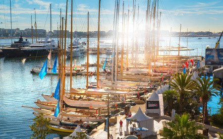 super yacht: CANNES, FRANCE - 19 SEPTEMBER, 2016:   Old Port Vieux Port in the city of Cannes at sunset. Lots of sailing boats and power yachts anchored during the Sailing regatta.