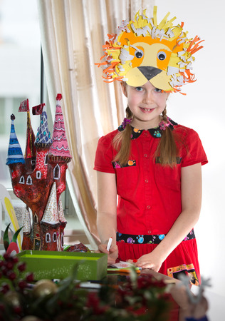 Little girl demonstrating her art craft works, Paper masher fairy castle and Lion mask she made. Educational and creative concept. Stock Photo