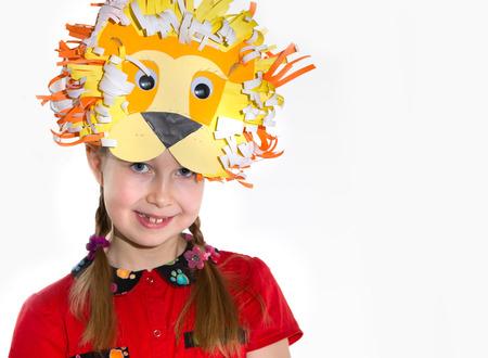 어린 소녀 그녀의 예술 공예품 작품, 종이 masher 요정 성 및 그녀가 만든 사자 마스크를 시연. 교육 및 창조적 인 개념입니다.