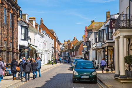 RYE, UK - 1 MAY, 2016: High street of Old Rye town with periodic buildings, lots of people and cars parked on side. Editorial
