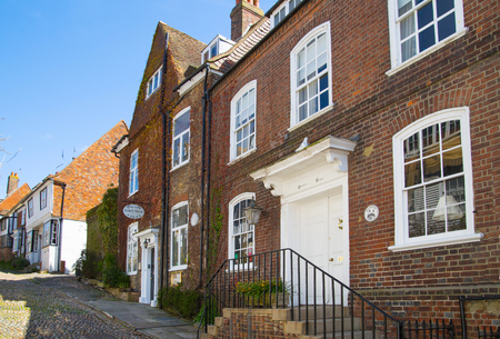 latticed: RYE, UK - 1 MAY, 2016: Old street of Rye town with periodic buildings. Mermaid Street showing typically steep slope and cobbled surface