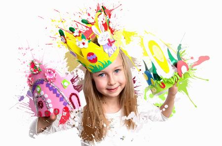 niños sonriendo: Niña que demuestra su trabajo artesanal, sombreros de Pascua y la corona.