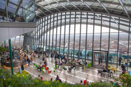 heist: LONDON, UK - APRIL 22, 2015: People in the restaurant of the Sky Garden Walkie-Talkie building. Viewing platform is heist UK garden, locates at the 32 floor and offers amazing skyline of London city.