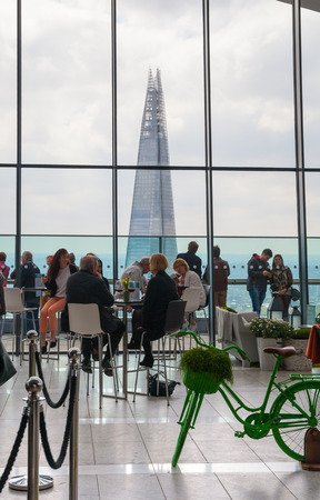 heist: LONDON, UK - APRIL 22, 2015: People in the restaurant of the Sky Garden Walkie-Talkie building. Viewing platform is heist UK garden, locates at the 32 floor and offers amazing skyline of London city.