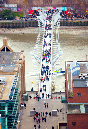 LONDON, UK - DECEMBER 19, 2016: Millennium foot bridge over the River Thames and office people walking through