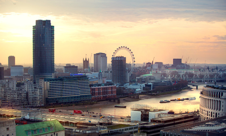 LONDON, UK - DECEMBER 19, 2016: London at sunset, view at the Westminster side of the city, River Thames and London bridge sun reflection