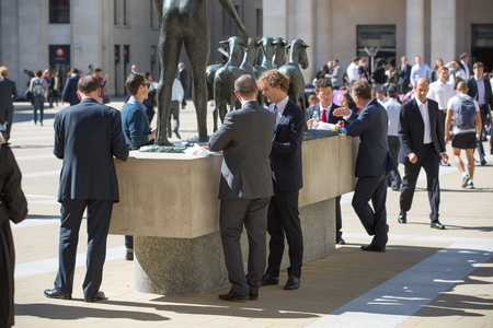 office life: LONDON, UK - JUNE 30, 2014: Office workers al lunch time in the square of St. Pauls cathedral. City of London business life