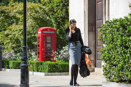 LONDON, UK - SEPTEMBER 10, 2015: Office workers and people walking in the st. Pauls cathedral park in lunch time. City of London business life