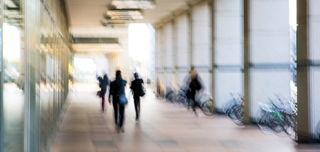 arhitecture: Abstract, blurred image of people walking via long tunnel with light at the background. Stock Photo
