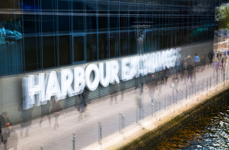 Multiple exposure effect image. Office workers walking against of Harbour Exchange sign Stock Photo