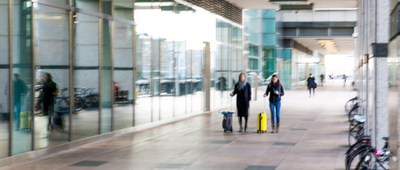 arhitecture: Abstract, blurred image of people walking via long tunnel with light at the background. e end. Business and modern life concept.