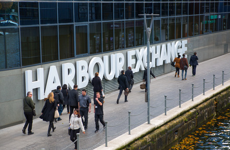 arhitecture: LONDON, UK - November 16, 2016: Canary Wharf. Office workers walking against of Harbour Exchange sign