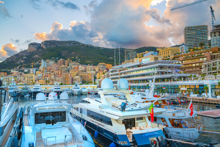 principality: Monaco, Monte Carlo - September 16, 2016: Sunset in Principality of Monaco. View of the seaport and the city of Monte Carlo with luxury yachts and sail boats