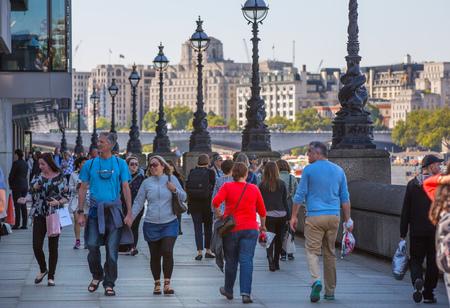 british touring car: LONDON, UK - SEPTEMBER 10, 2015: Embankment of River Thames with lots walking people Editorial