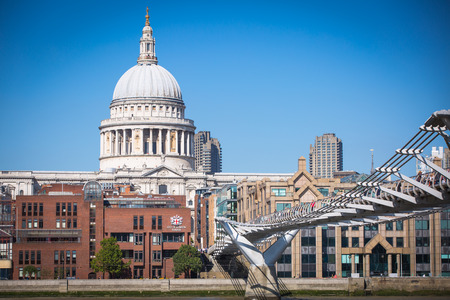 st  paul   s cathedral: LONDON, UK - SEPTEMBER 10, 2015: Millennium bridge with lots of people walking against of St. Paul s cathedral