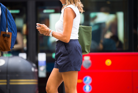 Young woman walking with mobile phone. Londoners at warm summer day. UK