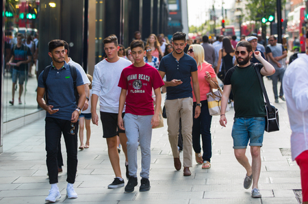 street life: London, UK - August 24, 2016: Young attractive men walking in Oxford street, the main destination of Londoners for shopping. Modern life concept Editorial