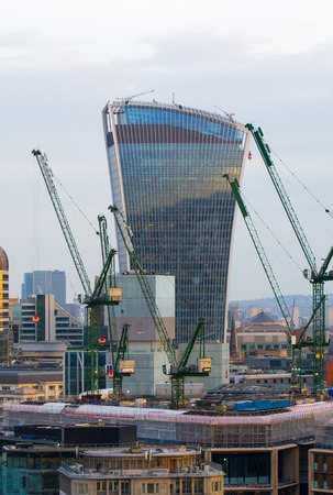 sunset city: London, UK - December 19, 2016: City of London business aria view at sunset. View includes Walkie-Talkie building and lots of cranes. City of London the leading financial centre in the Europe. Editorial