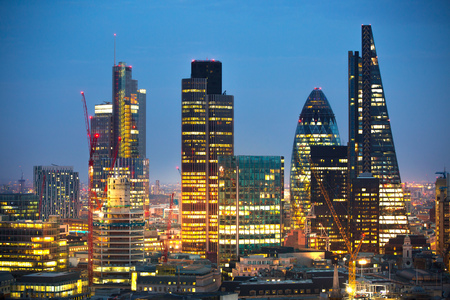 sunset city: London, UK - December 19, 2015: City of London at sunset with lights and reflection. View at the business and banking aria with modern skyscrapers