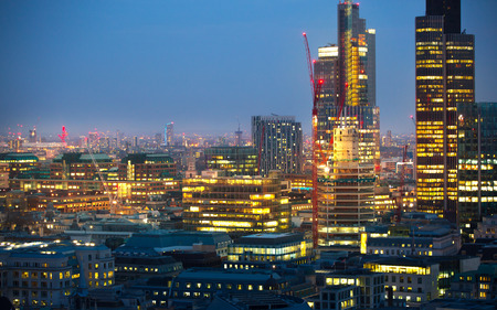 City of London at sunset with lights and reflection. View at the business and banking aria with modern skyscrapers