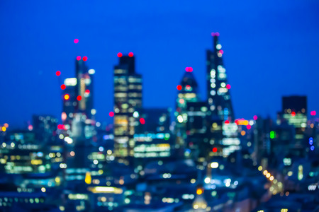 City of London at sunset with lights and reflection. View at the business and banking aria with modern skyscrapers. Blurred image for background
