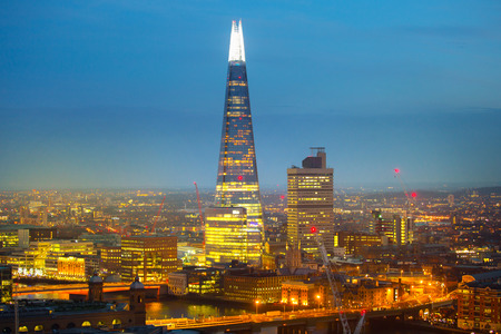 shard: London, UK - December 19, 2015: London at night. Shard of glass and London bridge with lights and reflection.