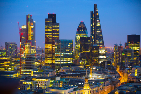 London, UK - December 19, 2015: City of London at sunset with lights and reflection. View at the business and banking aria with modern skyscrapers
