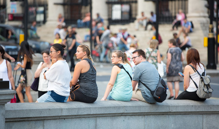 square image: London, UK - 24 August, 2016: Trafalgar square with lots of people sitting on the stairs. Blurred image Editorial