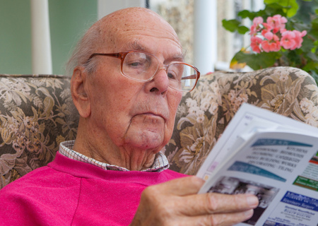 95 years old English man sitting in chair in domestic environment. Health and care concept