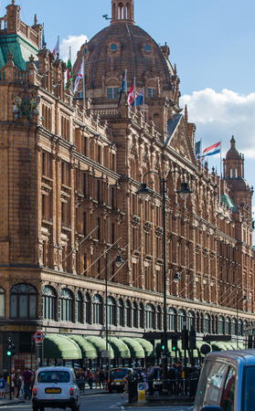 LONDON, UK - SEPTEMBER 8, 2016:  Harrods department store and Brompton road view with cars, taxies and people