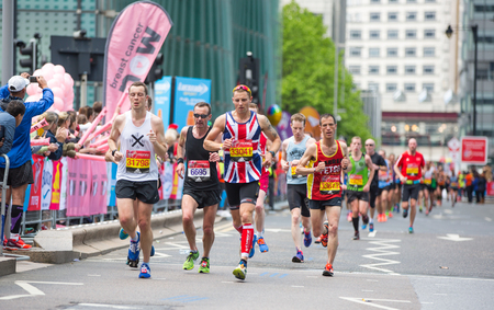 London, UK - April 23, 2017: Lots of people running in London Marathon.  People cheering the sportsmen in Canary Wharf aria
